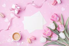 Morning cup of coffee, cake macaron, gift box, envelope and spring tulip flowers on pink background. Beautiful breakfast for Women. Day, Mother day. Flat lay stock images