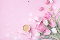 Morning cup of coffee, cake macaron, gift box and spring tulip flowers on pink background. Beautiful breakfast for Women day