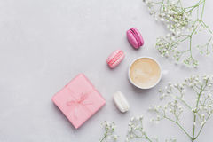 Morning cup of coffee, cake macaron, gift or present box and flower on light table from above. Beautiful breakfast. Flat lay. Morning cup of coffee, cake royalty free stock photography