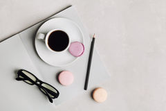 Morning cup of coffee, empty notebook, pencil, glasses and cake macaron on gray desk overhead view. Beautiful breakfast. Flat lay. Stock Image