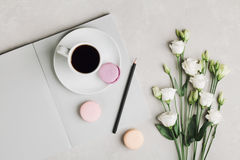 Morning cup of coffee, empty notebook, pencil, white flowers and cake macaron on gray table from above. Beautiful breakfast. Stock Photography