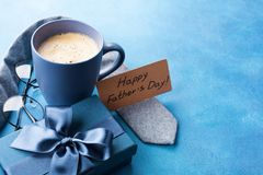 Morning cup of coffee, gift box, necktie and eyeglasses on blue table for greeting on Happy Fathers Day. Stock Photos