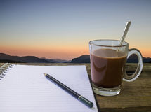 Morning cup of coffee and notebook pencil with mountain Royalty Free Stock Image