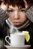 Morning cup of tea. Young beautiful woman in knitted scarf,  with the cup of hot tea Royalty Free Stock Photo