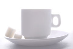 Morning cup of tea. White china cup of tea and plate with lump sugar on white Royalty Free Stock Photography