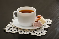 Morning cup of tea, Turkish delight in a saucer on the black desk.  Royalty Free Stock Photography