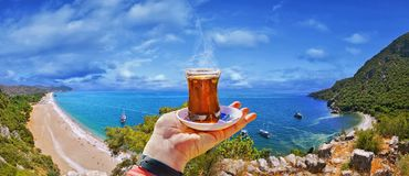 Morning cup of tea with view of colorful panoramic Olympos beach stock image
