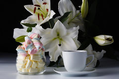 Morning cup of tea, white lily, colored marshmallow Stock Images