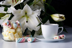 Morning cup of tea, white lily, colored marshmallow Stock Photo