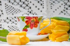 Morning cup of tea with yellow tulips Royalty Free Stock Photos