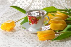 Morning cup of tea with yellow tulips Stock Images