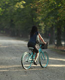 Morning cycling. Young woman riding a bicycle in a park in the morning Royalty Free Stock Images