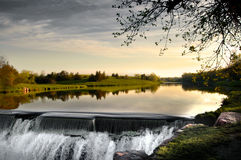 Morning at the dam. Water flowing over a dam with early morning reflections in the creek above Royalty Free Stock Photos