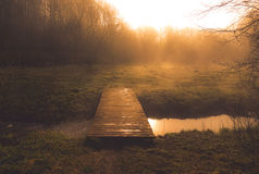 Morning dawn with mist near water stream and footbridge Royalty Free Stock Photos