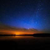 Morning dawn on starry background sky reflected in the water Stock Photography