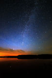 Morning dawn on  starry background sky reflected in the water o Royalty Free Stock Image