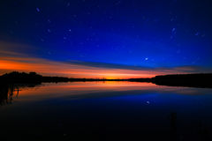 Morning dawn on  starry background sky reflected in the water o Royalty Free Stock Photography