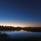 Morning dawn on a starry background sky reflected in the water o Royalty Free Stock Photography