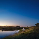 Morning dawn on a starry background sky reflected in the water o Stock Images