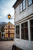 Morning in Den Gamle By - Aarhus, Denmark. An old street light is still lit as dawn arrives at the old town (Den Gamle By in Danish) with its timbered houses Royalty Free Stock Photography