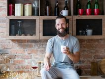 Morning drink warmth energy happiness hipster cup. Morning drink warmth and energy. Rise and shine. Happiness. Smiling bearded hipster sitting on kitchen counter royalty free stock photos