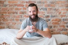 Morning drink warmth smiling hipster bed cup. Morning drink warmth and energy. New day. Rise and shine. Smiling hipster in bed with cup of beverage stock photo