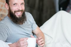 Morning drink warmth smiling hipster bed cup stock photo
