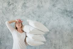 Morning duties woman arranging bedding pillows. Morning duties. Arranging bedding. Tired young woman holding pile of pillows. Copy space on grey background stock images