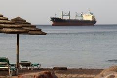 Morning on Eilat public beach. Large cargo Ship on horizon. Royalty Free Stock Photos