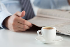 Morning espresso cup with busiessman reading newspaper on background. Cup of morning coffee on worktable with business analyst hold in hands and read newspaper royalty free stock photos