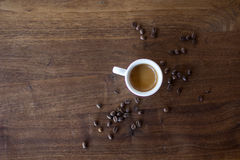 Morning Espresso. Freshly brewed espresso surrounded by coffee beans Royalty Free Stock Photography