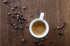 Morning Espresso. Freshly brewed espresso surrounded by coffee beans Royalty Free Stock Photos