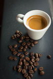 Morning Espresso. Espresso surrounded by coffee beans Royalty Free Stock Image