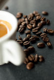 Morning Espresso. Espresso surrounded by coffee beans Royalty Free Stock Photo