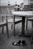 Morning Evidence. An empty glass of red wine and black high heel shoes sit abandoned on the patio come the gray, cloudy morning.  Wooden tables and benches sit Royalty Free Stock Image