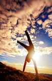Morning exercise. Sporty girl standing on hands outside royalty free stock image