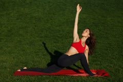 Morning exercise. Girl on the red carpet. Woman practices yoga in nature Stock Images