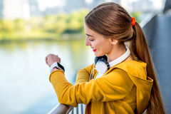 Morning exercise in megacity. Young sport woman in yellow sweater looking at smart watch on the modern bridge with skyscrapers on the background. Morning Royalty Free Stock Images