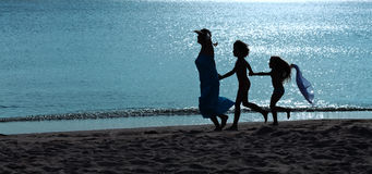 Morning exercise - woman and kids running on the beach stock images