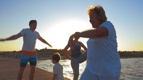 Morning Exercises of a Big Family. Slow motion shot of a family doing morning exercises on a sea pier stock video