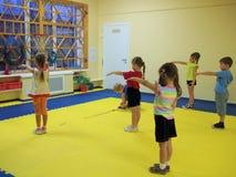 Morning exercises in kindergarten. Children doing morning exercises in gym hall in kindergarten Royalty Free Stock Images
