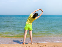Morning exersise on the beach. Yong woman doing morning exersise on the beach stock photography