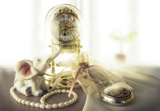 Morning of a fair lady. A picture of exquisite alarm clock, a string of pearls and delicate accessories Stock Image