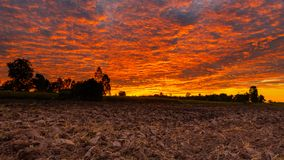Morning fire sky and scattered clouds with trees and agricultural field as silhouette foreground. Thailand stock photo