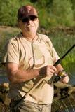 Morning fisherman. Old senior smiling in rising sun, holdinh his fishing rod Stock Photo