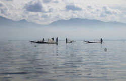 Morning fishers at Inle Lake. Early morning scenery in mist with sillhouettes of fishers at Inle lake in Myanmar Royalty Free Stock Photo