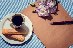Morning. Flat lay table with a cup of coffee, plate with cookies, notebook, pen and flowers eustoma, vintage filtered and toned. stock image