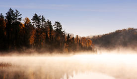 Morning Fog. A morning fog in northern MN on the gunflint trial, near bearskin lodge.  The sky is blue, the leaves are turning colors.  The season is fall, and Royalty Free Stock Images