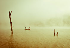 Morning fog. Boat with fishing people covered with the fog between tree trunks Stock Image