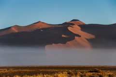 Morning fog below the sand dunes, Sossusvlei National Park, Namibia Royalty Free Stock Images